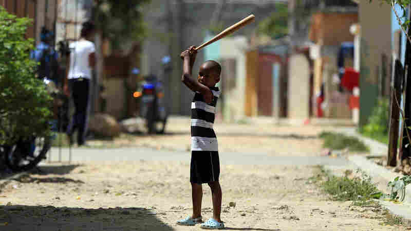 A boy is ready to take a swing on the streets of San Pedro de Macoris, a provincial capital of the Dominican Republic.