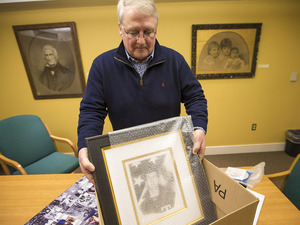 David Cline places the portrait of his uncle Sgt. Robert Dakin into a box with other memorabilia. Dakin was declared missing 65 years ago in Korea. It wasn't until recently that his remains were identified, and this past December, they were returned to his family.