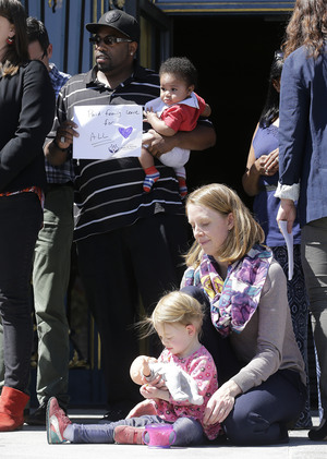 Alphonzo Jackson holds his 6-month-old son, Isaiah, behind Kim Turner and her daughter Adelaide Turner Winn during a rally supporting paid family leave at City Hall in San Francisco on Tuesday.
