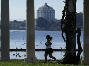 A woman jogs in Oakland, Calif., last February. Healthier lifestyles may be a reason why poor people live longer in some cities than others.