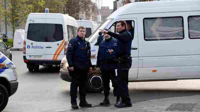 Belgian police officers stand in Albert I square in Brussels, where authorities arrested Mohamed Abrini, a key Paris attacks suspect, on Friday.