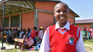Faye, 14, a pupil at the Sekenani Girls' School proudly shows visitors around the classrooms and grounds.