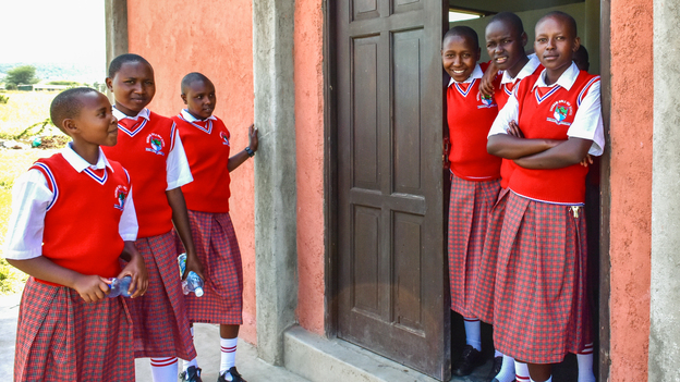 Students from the Sekenani Girls Secondary School gather outside their dormitory after lunch. The new school is the first high school for girls in the Maasai region. (Harriet Constable for NPR)