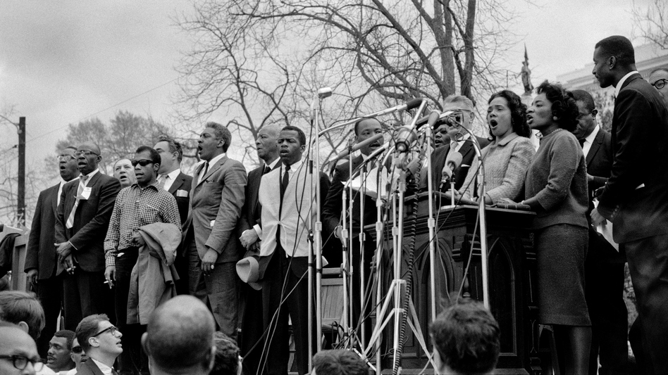 "Civil rights leaders, including Dr. Martin Luther King, Jr., sing ""We Shall Overcome"" at the conclusion of the Selma to Montgomery civil rights march in 1965. (Getty Images)"