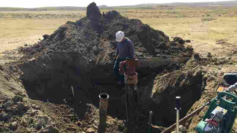 A contractor prepares to cut off the top of a coal bed methane well near Gillette, Wyo., in 2015. It's one of thousands of abandoned, plugged wells sprinkled throughout Wyoming and Colorado.