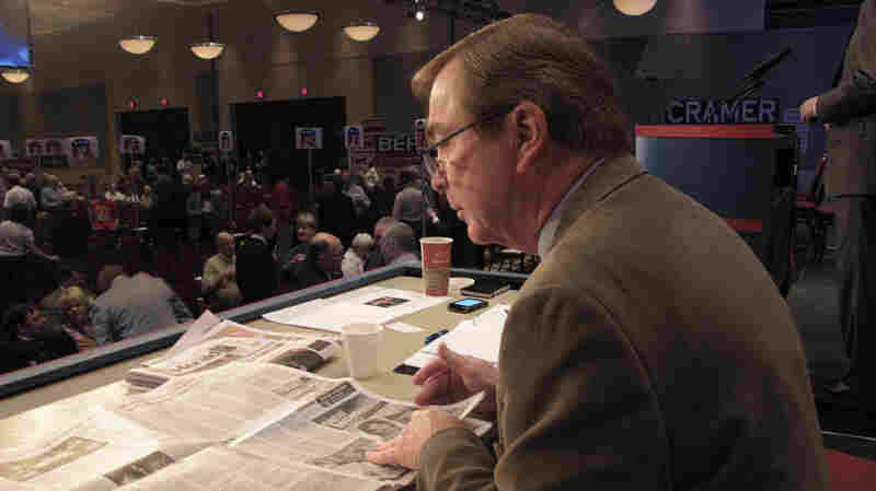 Curly Haugland, a Bismarck businessman and North Dakota representative on the Republican National Committee, reads a newspaper on the North Dakota state Republican convention stage in 2010.