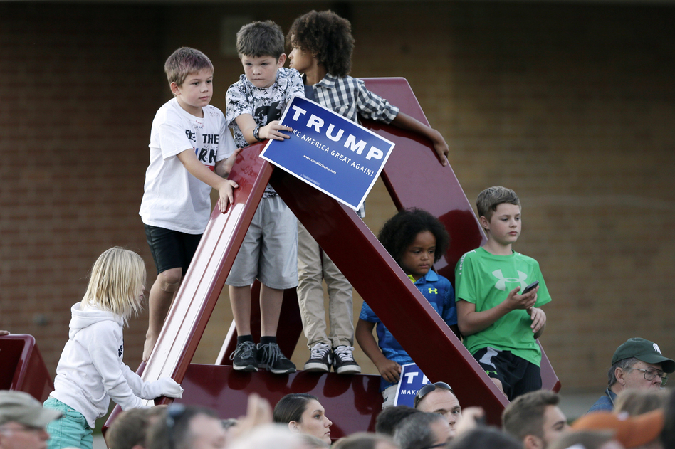 Children climb on a sculpture as Republican presidential candidate Donald Trump speaks during a rally at Urbandale High School in Urbandale, Iowa. (Charlie Neibergall/AP)