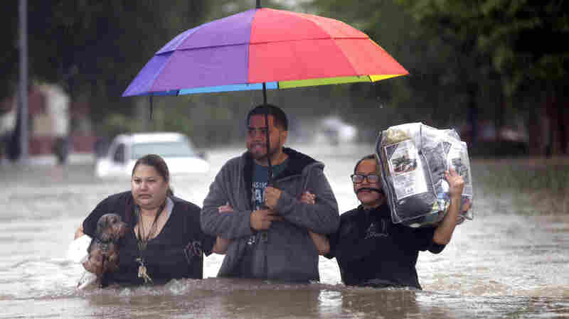 Felix Yanez (center) helps Lucy Olvio (right) and Judy, who declined to give her last name, wade through floodwaters as they leave their flooded apartment complex Monday in Houston.