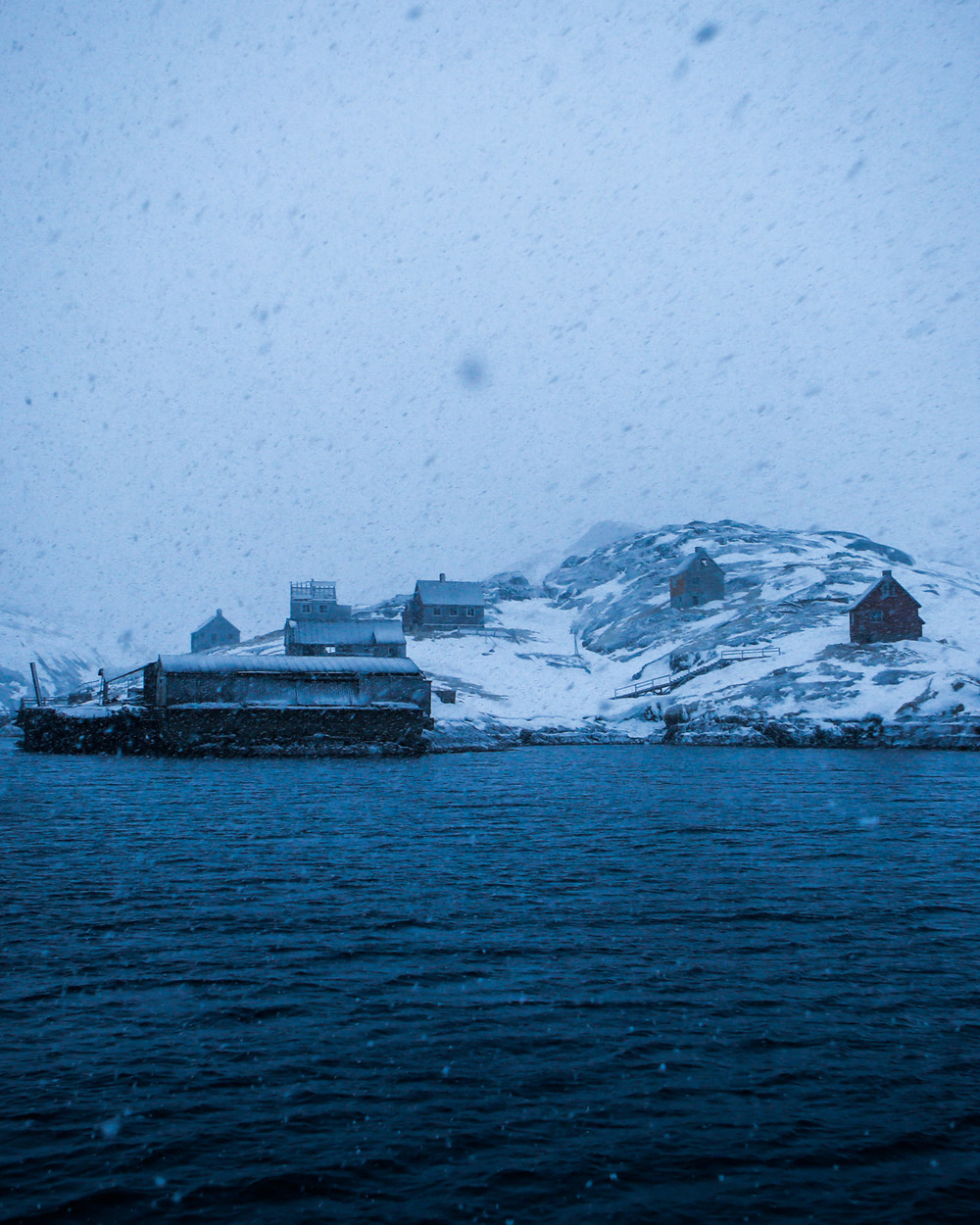 Kangeq's old wharf and houses appear ghostlike through a late winter snowstorm.