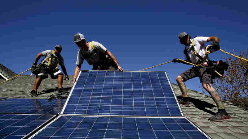 Workers install solar panels on the roof of a home in Camarillo, Calif., in 2013. San Francisco has recently decided to start requiring rooftop solar systems — electrical or heating — on new construction up to 10 stories tall.