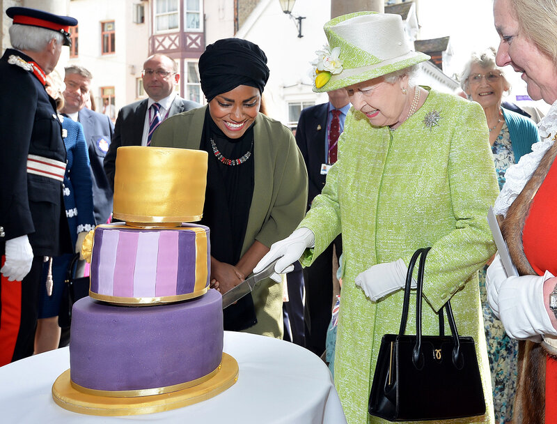 Britain's Queen Elizabeth II cuts into a birthday cake baked by Nadiya Hussain (left), winner of The Great British Bake Off, during celebrations of the queen's 90th birthday in Windsor, England.