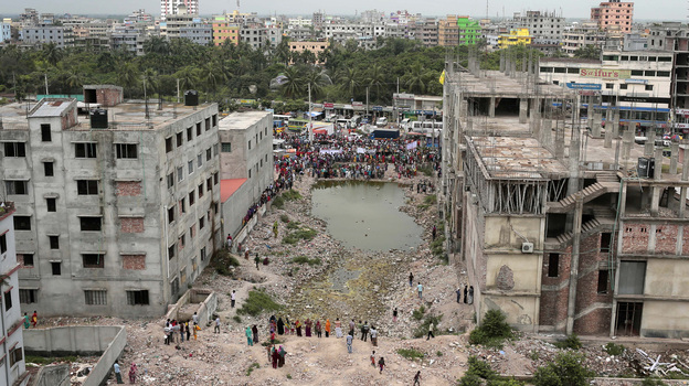 Relatives of the victims stand at the site of the Rana Plaza building, in this 2015 photo. More than 1,100 people died when the eight-story factory building collapsed. (AP)