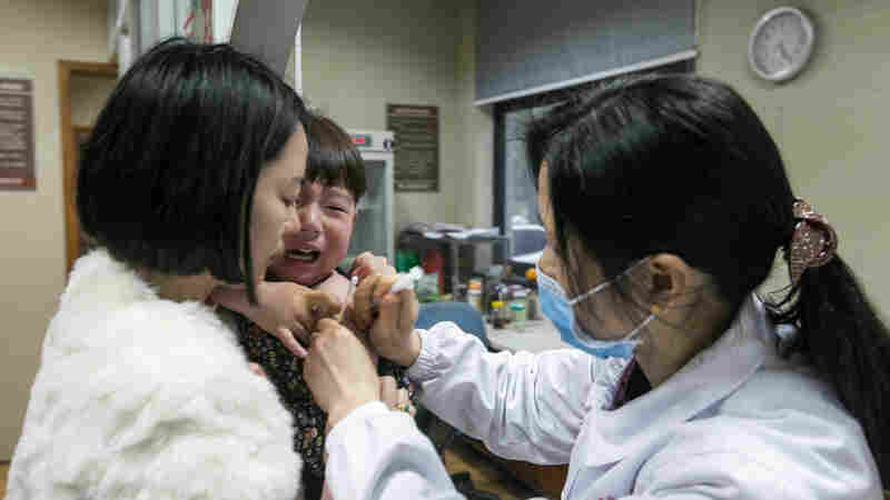 At a Chinese hospital, a woman holds her child, who's receiving a rabies vaccine after being scratched by a cat. Vaccines against rabies were among the millions that were part of a newly discovered racket, reselling vaccines that hadn't been refrigerated.