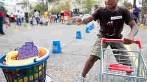 "A child runs a shopping cart relay during an Education Department summer enrichment event, ""Let's Read, Let's Move."" The 2012 event was part of a summer initiative to engage youths in summer reading and physical activity, and provide them information about healthy, affordable food. Many efforts underway are aimed at getting people to think anew about their daily habits."