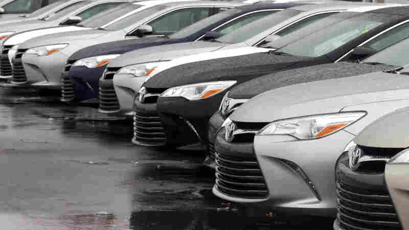 Toyota cars for sale are parked at a dealership in Danvers, Mass. Federal Reserve policymakers left rates unchanged Wednesday, which should keep down the costs of car loans and other borrowing.