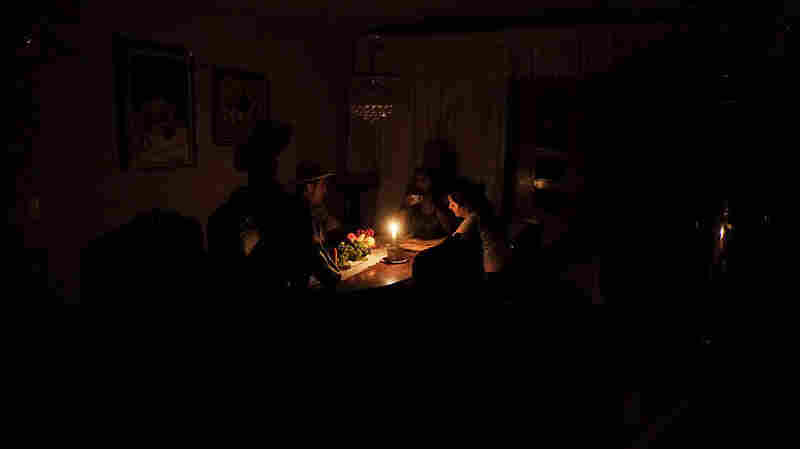 A family sits at a candlelit table in the state of Barinas, 370 miles west of Caracas, on Monday.