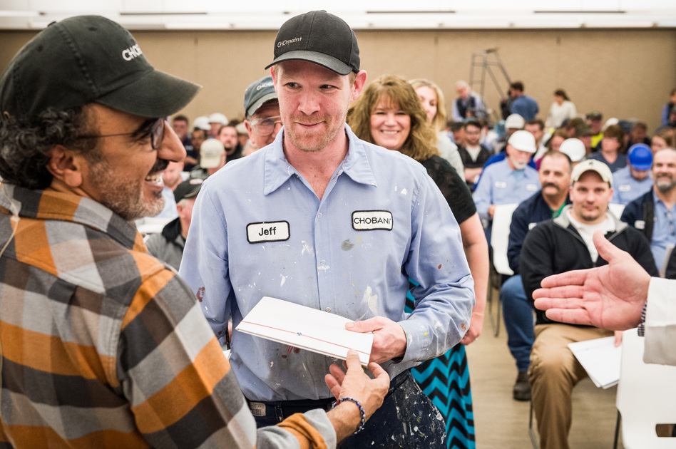 Chobani CEO Hamdi Ulukaya (left) presents an employee with shares of the company on Tuesday at the Chobani plant in New Berlin, in upstate New York. (Johannes Arlt)