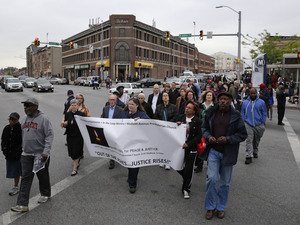 People march in the Penn North neighborhood of Baltimore on Wednesday — the anniversary of the funeral of Freddie Gray.