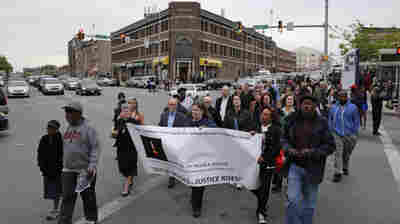 People march in the Penn North neighborhood of Baltimore on Wednesday — the anniversary of rioting following the funeral of Freddie Gray.