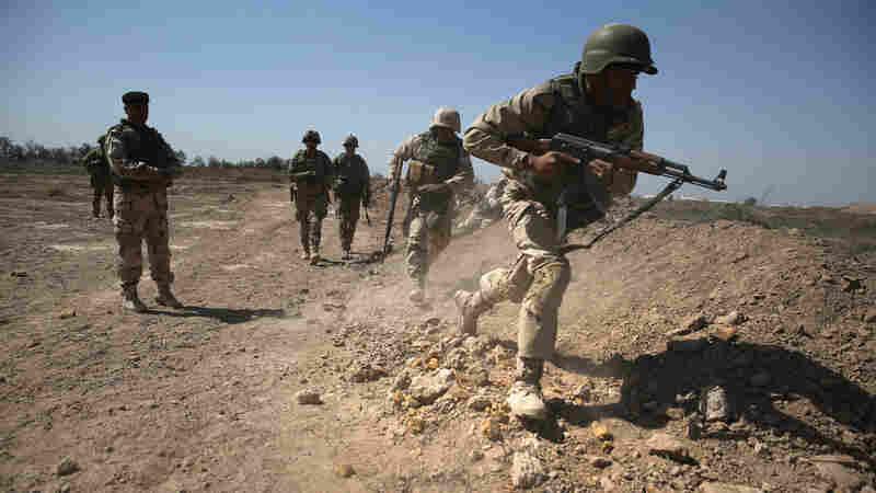 Army trainers conduct drills at a military base in Taji, Iraq last year.