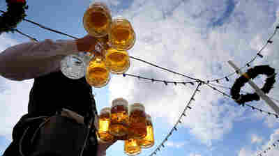 A waiter carries beers at the Theresienwiese fair grounds of the Oktoberfest beer festival in Munich, southern Germany, last September. For centuries, a German law has stipulated that beer can only be made from four ingredients. But as Germany embraces craft beer, some believe the law impedes good brewing.