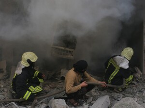 Firefighters combat a blaze on April 29, after regime helicopters targeted a medical center in an opposition-controlled region of Aleppo, Syria.