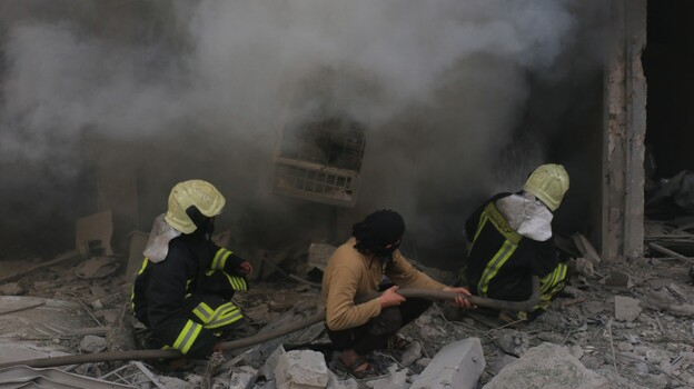 Firefighters combat a blaze on April 29, after regime helicopters targeted a medical center in an opposition-controlled region of Aleppo, Syria. (Getty Images)