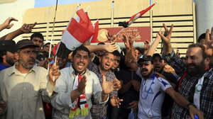 Supporters of Shiite cleric Muqtada al-Sadr raise the Iraqi flags outside parliament in Baghdad's Green Zone on Saturday. Protesters climbed over the blast walls and stormed the Parliament building.