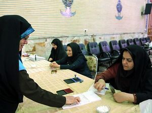 An Iranian election official checks identities during a second round of parliamentary elections at a polling station in Shahriar district of Tehran, Iran on Friday.