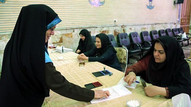 An Iranian election official checks identities during a second round of parliamentary elections at a polling station in Shahriar district of Tehran, Iran on Friday. (Getty Images)