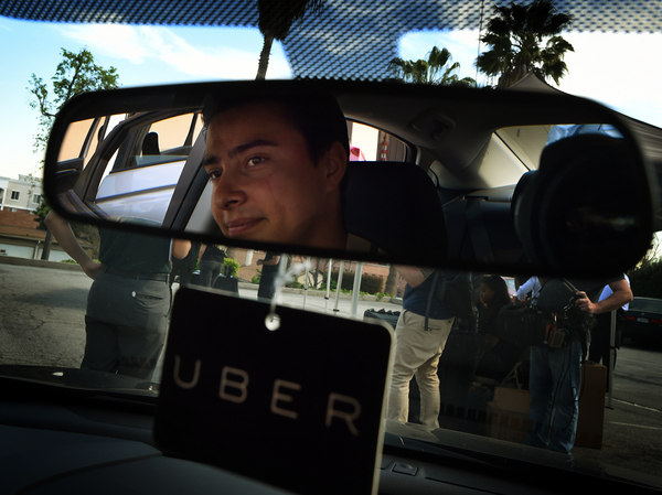"Jesse Vega checks out a vehicle at an Uber ""Work On Demand"" recruitment event March 10 in South Los Angeles. The company is researching ways to get rid of its surge pricing, a feature that drivers like but that can make costs unpredictable for consumers."