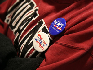 A supporter of Democratic presidential candidate Hillary Clinton wears campaign buttons as she listens to former President Bill Clinton at an event in Indiana.
