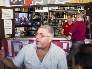 A barman and a customer watch Alejandro García Padilla, governor of Puerto Rico, giving a speech on a television screen in a bar in San Juan, Puerto Rico, on Sunday.