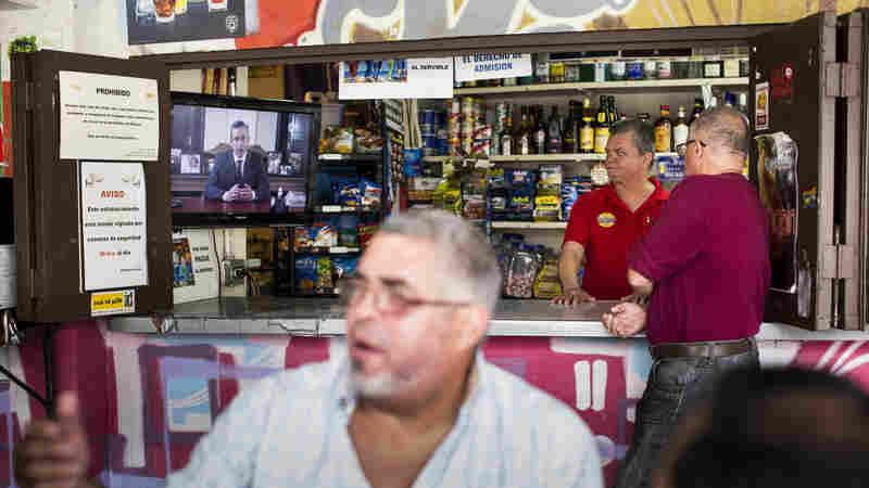 A barman and a customer watch Alejandro García Padilla, governor of Puerto Rico, giving a speech on a television screen in a bar in San Juan, Puerto Rico, on Sunday.