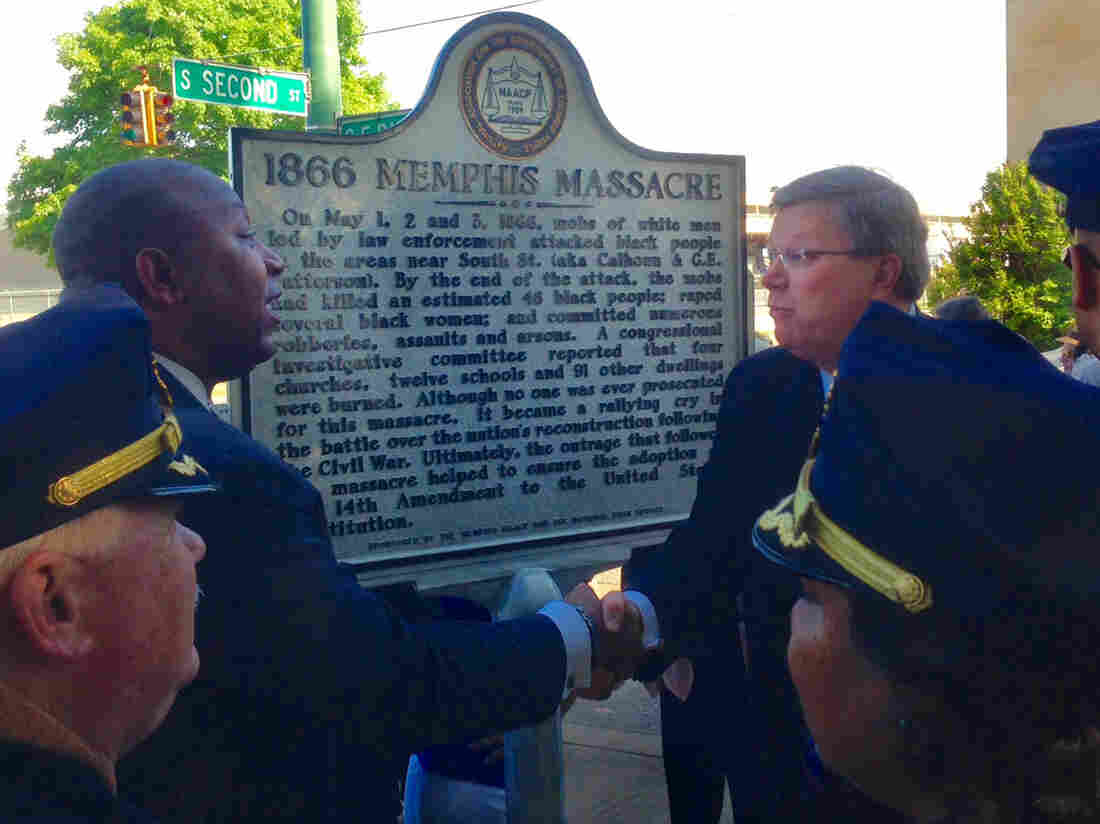 Memphis law enforcement looks on as Rev. Keith Norman (left), president of the Memphis branch of the NAACP, shakes hands with Memphis Mayor Jim Strickland in front of the new historical marker.