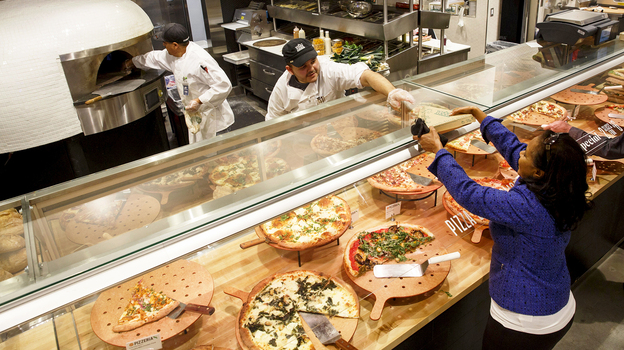 A customer receives a slice of pizza from the prepared food section of the new Whole Foods Market Inc. store in downtown Los Angeles. Prepared foods sold at supermarkets, big-box and convenience stores are a bigger and bigger portion of those companies' profits. (Bloomberg via Getty Images)