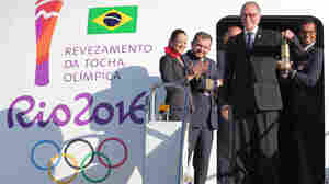 The Brazilian Olympic Committee president shows the lantern containing the Olympic flame brought from Greece as he deplanes in Brasilia on May 3. The three-month torch relay across Brazil will end at the opening ceremony on Aug. 5 at Maracana stadium in Rio.