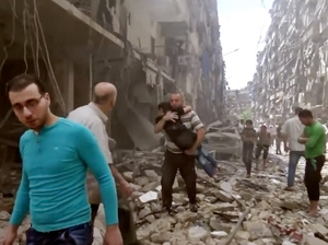 A man carries a child after airstrikes hit Aleppo, Syria last month.