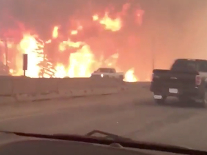 This photo shows flames from a wildfire along Highway 63 in Fort McMurray, Alberta, on Tuesday. A wildfire engulfed homes and sent ash raining down on residents.