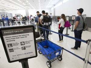 Faced with the prospect of long wait times at airports this summer, Homeland Security is boosting its checkpoint staffing. In this photo from December, passengers line up to go through security at the Fort Lauderdale-Hollywood International Airport.