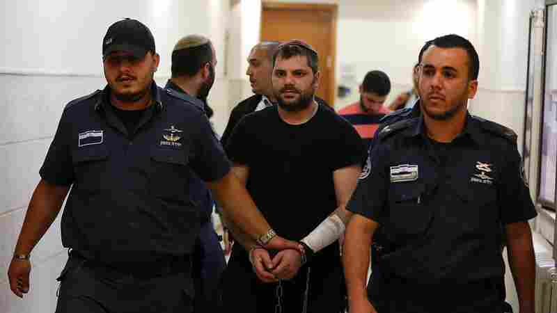 Israeli Yosef Haim Ben-David (center), the ringleader in the killing of Palestinian teenager Mohammed Abu Khdeir in 2014, is escorted by Israeli policemen at the district court in Jerusalem on Tuesday.
