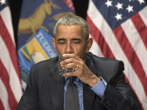 President Barack Obama drinks a glass of filtered Flint water during a meeting with federal officials at the Food Bank of Eastern Michigan in Flint, Mich. on Wednesday.