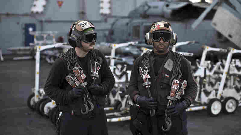 U.S. Navy air wing captains pause on the flight deck of the aircraft carrier USS Theodore Roosevelt last September. Every day, the steam-powered catapult aboard this massive ship flings American fighter jets into the sky, on missions to target the extremist Islamic State group in Iraq and Syria.