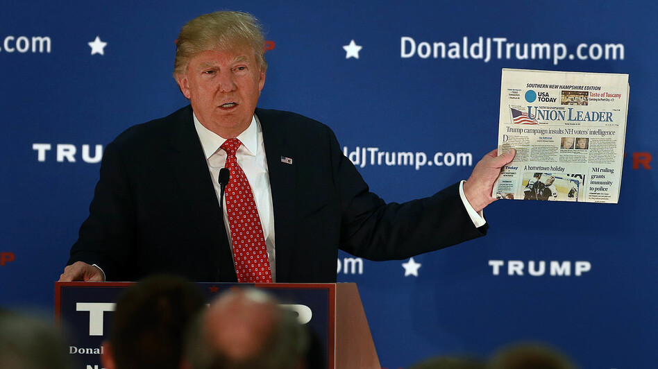 Republican presidential candidate Donald Trump frequently held up newspapers while on the campaign trail. (Boston Globe via Getty Images)