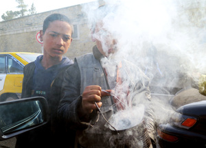 Young boys wave smoldering tin cans at cars in Kabul. The smoke from the seeds inside the cans is believed to ward off evil.
