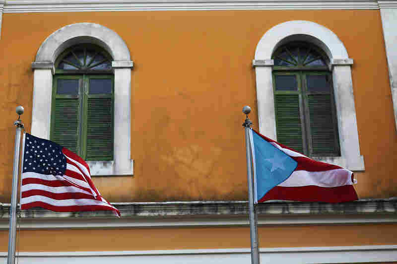 An American flag and Puerto Rican flag fly next to each other in Old San Juan a day after the Puerto Rican Governor Alejandro Garcia Padilla gave a televised speech regarding the governments $72 billion debt on June 30, 2015 in San Juan, Puerto Rico. The Governor said in his speech that the people will have to sacrifice and share in the responsibilities for pulling the island out of debt.