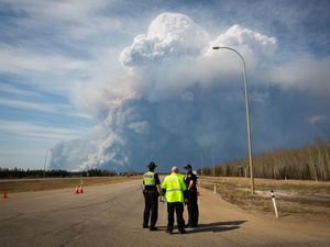 Officers look on as smoke from Fort McMurray's wildfires billow into the air in Alberta, Canada on Wednesday.