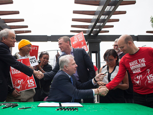 Seattle Mayor Ed Murray celebrated with supporters after signing a bill that raises the city's minimum wage to $15 an hour.