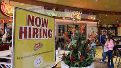 A restaurant posts a sign indicating they are hiring in Miami.