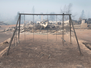 Swings were burned away in a residential neighborhood destroyed by a wildfire in Fort McMurray, Alberta, Canada on Friday.